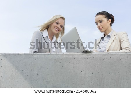Low angle view of businesswoman using laptop while standing with colleague on terrace against sky - stock photo