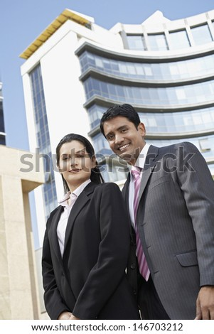 Low angle view of confident businesswoman and businessman standing in front of building - stock photo