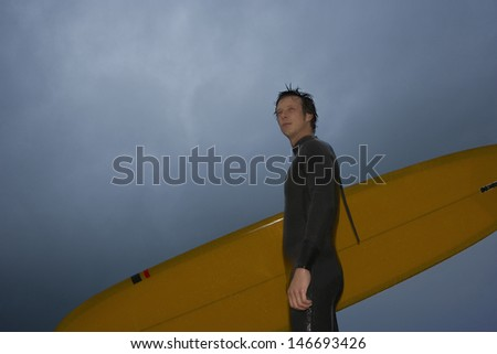 Low angle view of confident young man with surfboard looking away against cloudy sky at beach - stock photo