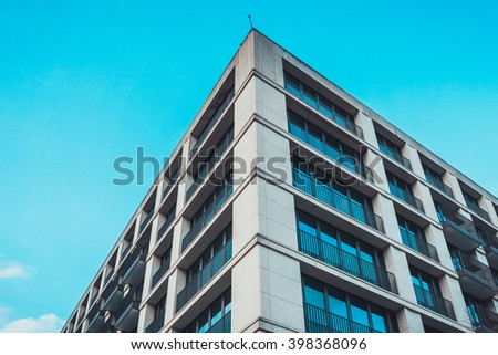 Low angle view of converging lines in the architectural design on rectangular modern residential condominiums under blue sky