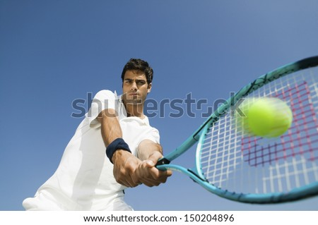 Low angle view of determined young man playing tennis against blue sky - stock photo