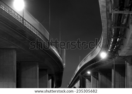 Low angle view of elevated road in black and white at night - stock photo