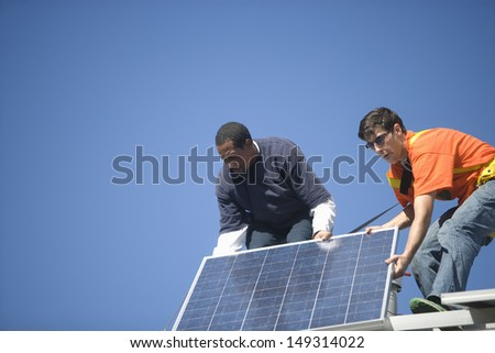 Low angle view of engineers fixing solar panel against blue sky - stock photo