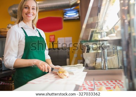 Low angle view of female worker cutting sandwich on counter in bakery - stock photo