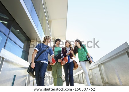 Low angle view of four university students on campus - stock photo
