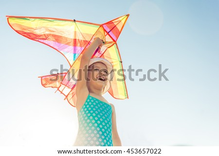 Low angle view of funny little girl in summer clothes holding a toy airplane, looking forward and smiling, sunny clear sky in the background - stock photo