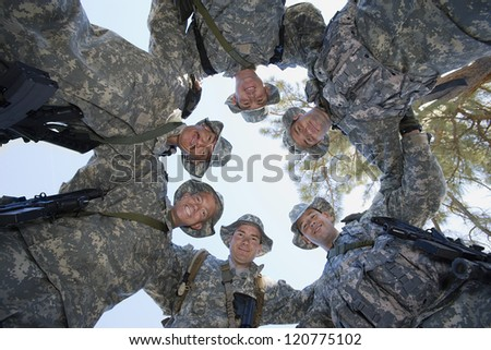 Low angle view of happy group of soldiers forming a huddle - stock photo