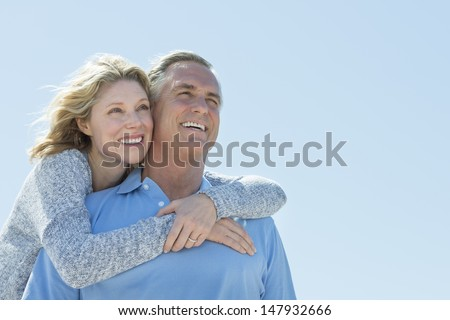 Low angle view of happy mature woman embracing man from behind while looking away against clear sky - stock photo