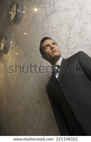 Low angle view of Hispanic businessman - stock photo