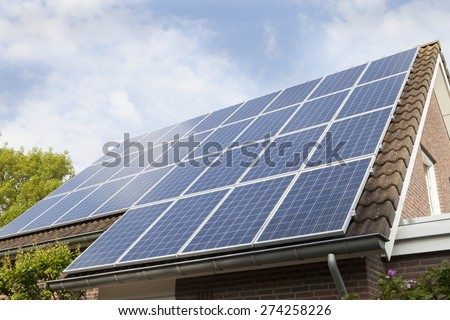 Low angle view of house roof covered with solar panels against sky - stock photo