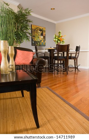 Low angle view of living room and dinning area, with hardwoods and flower and designer colors