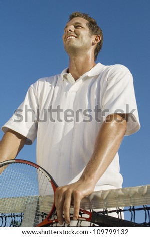 Low angle view of male tennis player standing against sky