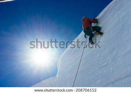 Low angle view of man climbing glacier - stock photo
