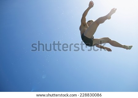 Low angle view of man flying through the air in a swimsuit against blue sky - stock photo