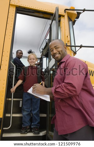 Low angle view of man writing on paper while boy getting down from school bus - stock photo