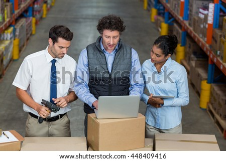 Low angle view of managers are looking a laptop in a warehouse