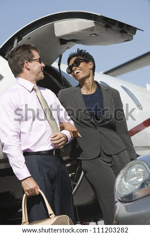 Low angle view of multi ethnic business couple standing together by airplane at airfield - stock photo