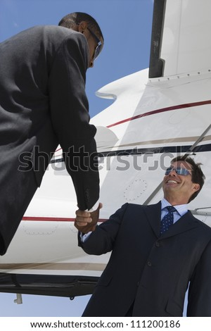 Low angle view of multi ethnic business people shaking hands against airplane tail at airfield - stock photo