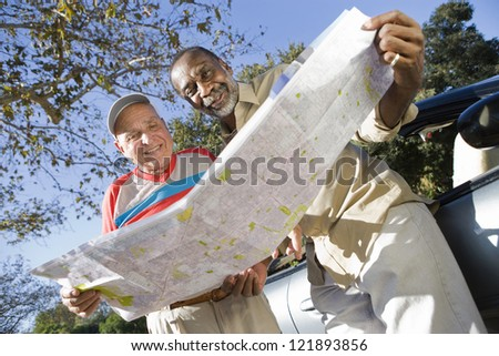 Low angle view of multi ethnic male friends with road map standing by the car - stock photo