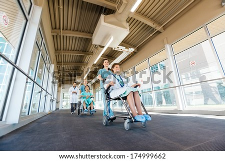 Low angle view of nurses pushing patients on wheelchairs while walking with doctor at corridor in hospital - stock photo