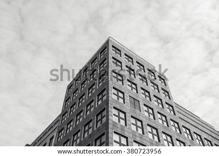 Low angle view of old warehouse loft building under fluffy white clouds in black and white - stock photo