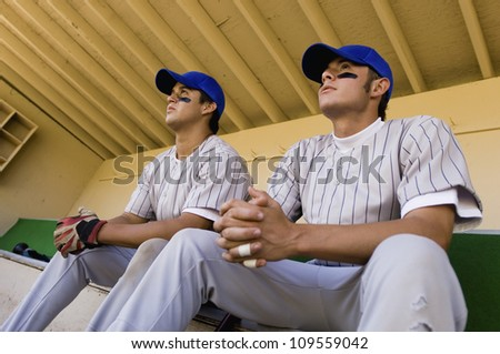 Low angle view of players watching the game intensely while sitting in dugout - stock photo