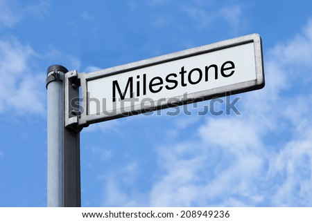 Low angle view of signpost with Milestone sign against sky - stock photo