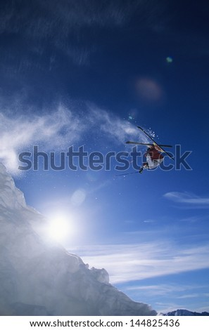 Low angle view of skier performing somersault against sky - stock photo