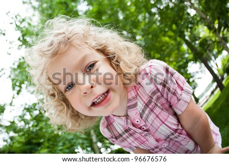 Low angle view of smiling child standing in spring park. Shot was taken with fisheye lens - stock photo