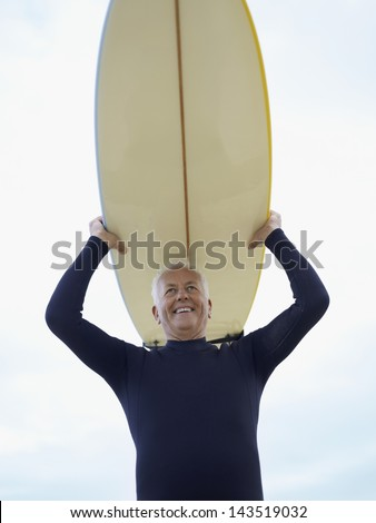 Low angle view of smiling senior man carrying surfboard over head against sky - stock photo