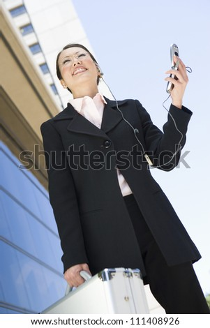 Low angle view of successful business woman using cell phone