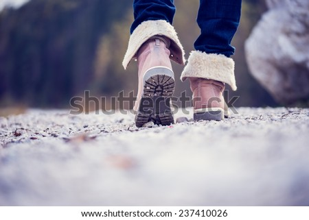 Low angle view of the feet of a woman in jeans and ankle high leather boots walking along a rural path away from the camera, vintage effect toned image. - stock photo