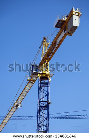 Low angle view of the rear side of a construction tower crane's rear side, displaying the heavy concrete weights that are keeping it balanced. - stock photo