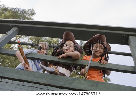 Low angle view of three kids in costumes looking through wooden railings - stock photo