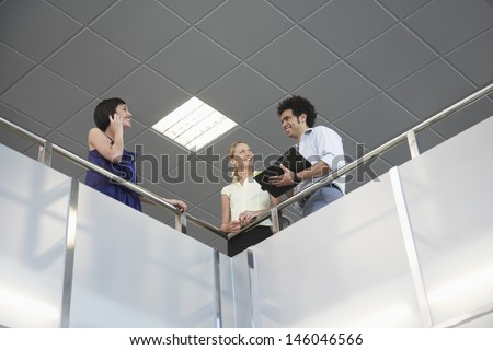 Low angle view of three smiling business colleagues with cellphone and planner at office balcony - stock photo