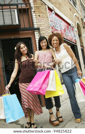 Low angle view of three young women holding shopping bags on the sidewalk - stock photo