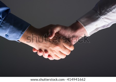 Low angle view of two businessmen hands shaking over dark gray background and light source at bottom side - stock photo