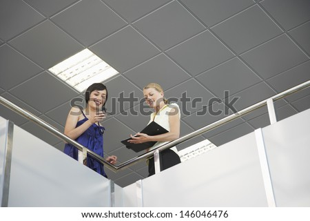 Low angle view of two smiling young business colleagues with cellphone and planner at office balcony - stock photo
