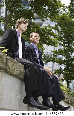 Low angle view of two young businessmen sitting on wall outside office