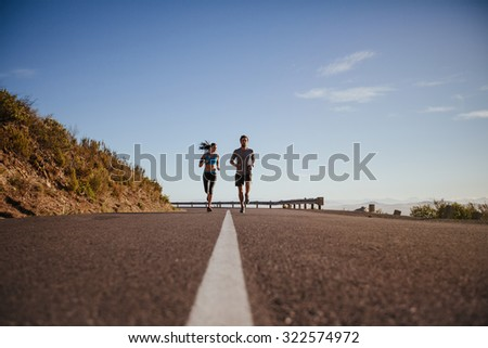 Low angle view of two young people running on road. Young couple jogging together on country road on summer day with lots of copy space. - stock photo