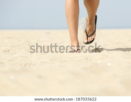 Low angle view of woman feet walking forward in flip flops on beach - stock photo