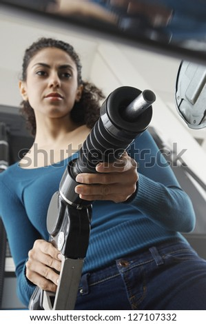 Low angle view of woman holding fuel nozzle and refueling car tank - stock photo