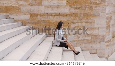 Low angle view of woman using laptop outdoors - stock photo