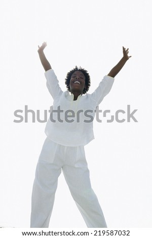 Low angle view of woman with hands raised - stock photo