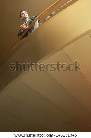 Low angle view of young businessman looking away while leaning on railing in office - stock photo