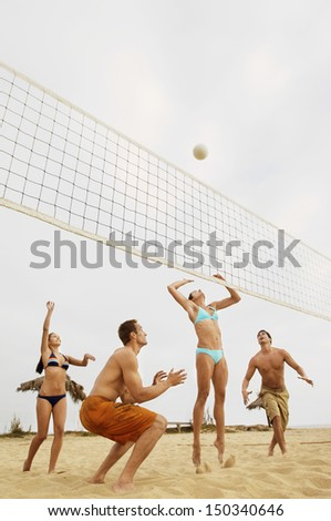 Low angle view of young friends playing volleyball on beach - stock photo