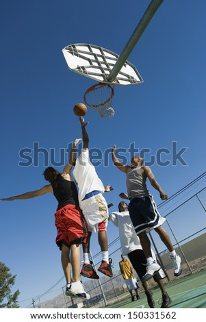 Low angle view of young men playing basketball on court - stock photo