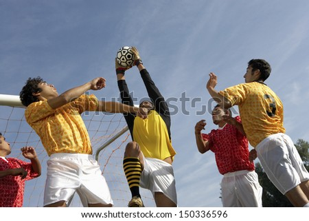 Low angle view of young players playing soccer against sky