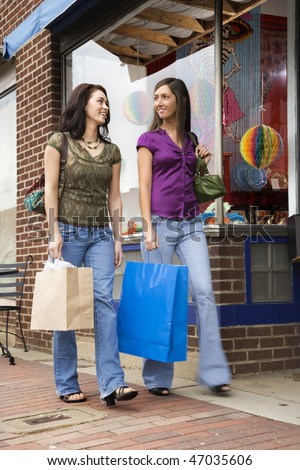 Low angle view of young women walking down a sidewalk lined with retail stores. They are both carrying shopping bags. Vertical shot. - stock photo