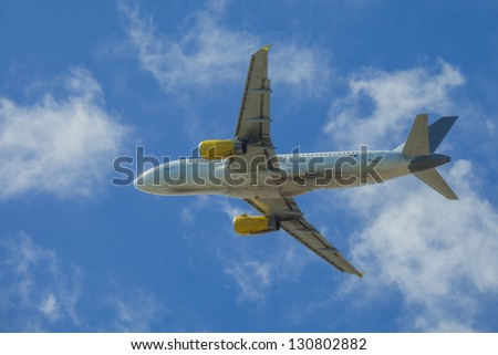 low angle view on an airplane in a blue sky - stock photo